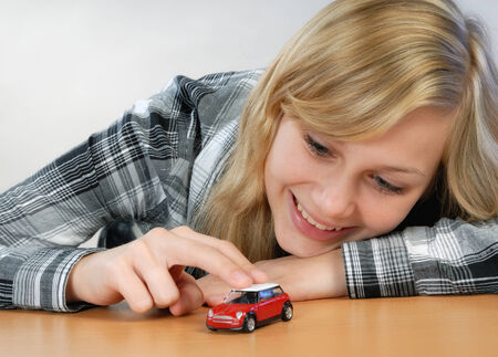 Happy blond girl plays with a toy car
