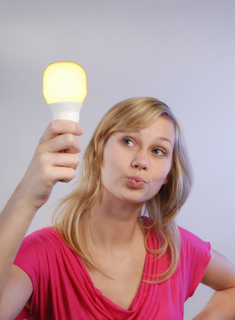 appraising: Young woman holding a energy saving lamp in hand