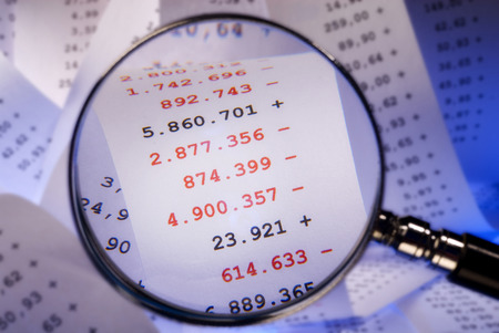 write off: Magnifier focused red numbers on a billing