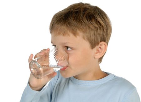 Boy drinks a glass of water