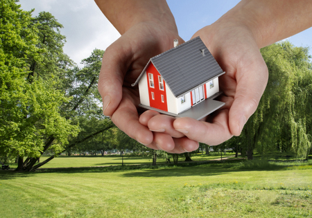 Hand with a house over a nice building plot  Stock Photo