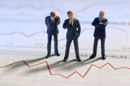 stock price: Businesspeople are standing in front of of the graphic of a stock price