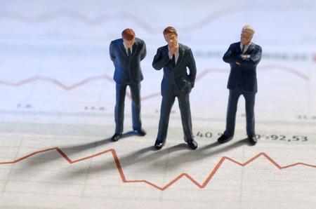 volatility: Los empresarios est�n de pie delante de la gr�fica de un precio de la acci�n Foto de archivo