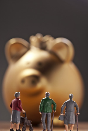 Three pensioners in front of a monumental piggy bank in gold with crown  Imagens