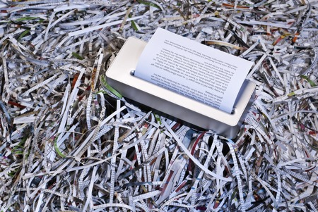 amounts: Shredder is surrounded by large amounts of shredded paper  Stock Photo
