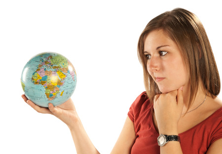 look for: Young blonde woman looks skeptical on the globe in her hand  Stock Photo