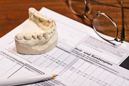 Plaster cast of teeth and treatment and cost plan by the dentist  The cost plan is labeled with the German word  Heil- und Kostenplan   Banque d'images