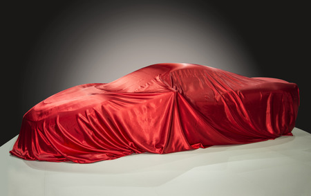 veiled: Sports car is covered with a red cloth Stock Photo