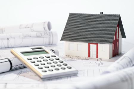 Baukosten von einem Architekturmodell symbolisiert, Architekturpläne und Taschenrechner.