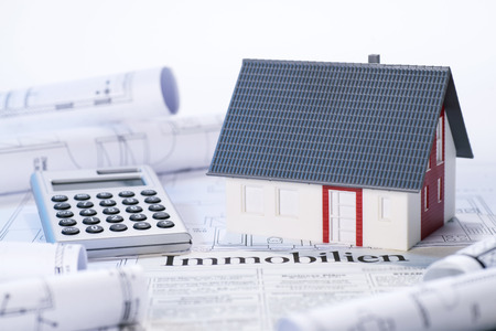 Model house, blueprints, calculator and real Estate adverts with the german word  Immobilien
