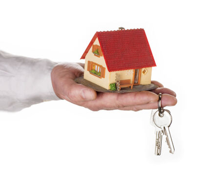 key handover: Closeup of a hand holding a model house and a key
