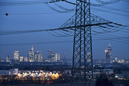 conduction: Skyline of Frankfurt in the evening with power pole and current conduction  Stock Photo