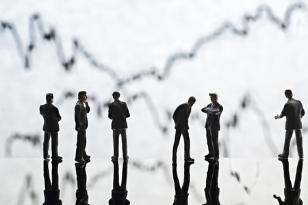Figures of businessmen standing in front of graphs symbolizing wavering exchange rates