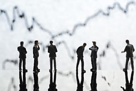 wavering: Figures of businessmen standing in front of graphs symbolizing wavering exchange rates