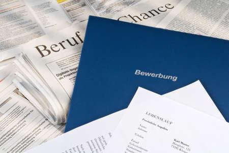 Application documents lying on a newspaper job ads