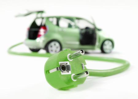 enchufe: Coche eléctrico con cable y enchufe, todo en color verde y aislados en blanco Foto de archivo