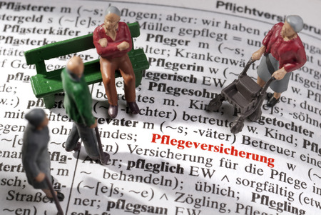 Topic Care insurance  Model figures of old people on an encyclopedia on which the German word  Pflegeversicherung  is to be read