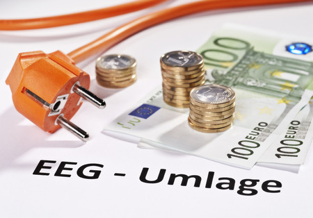 energy suppliers: Plug and Euro money with the german word  EEG-Umlage  in front as a symbol for the energy turnaround in Germany  Stock Photo