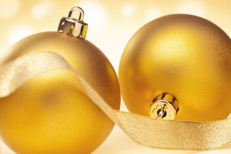 expectancy: Two golden Christmas baubles with a ribbon