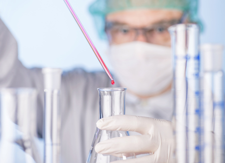 dripped: Scientist using pipette and flask in the laboratory.