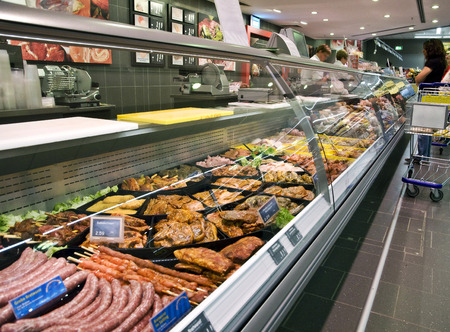refrigerated: Refrigerated counter with fresh meat in a supermarket
