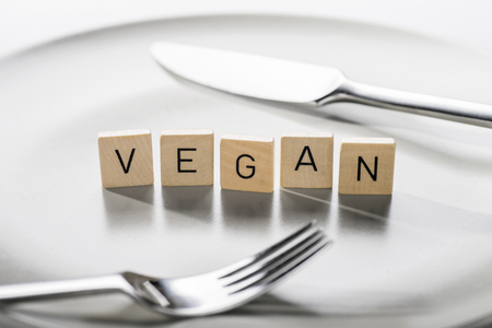 Plate with cutlery and the word vegan for vegan diet Stock Photo