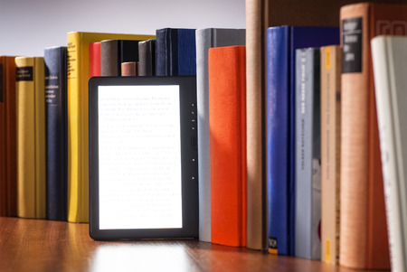 e book reader: E-book between a number of printed books. Stock Photo