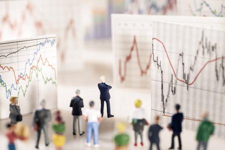 Banker steht auf einem Sockel von Münzen und schaut auf Boards mit verschiedenen Charts. Lizenzfreie Bilder