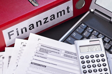 reckon: File folder labeled Finanzamt (tax office), forms, calculators and a computer as a symbol for the preparation of the tax return.