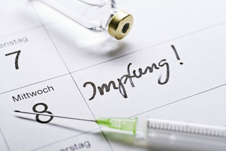 appointment book: Appointment book with the word Impfung for vaccination, a syringe and a vial of vaccine.