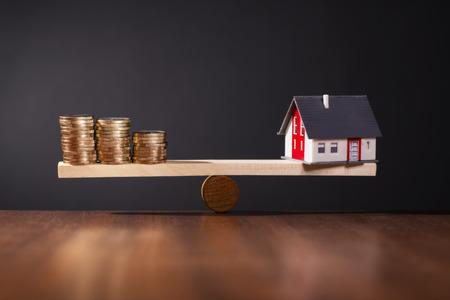 concepto equilibrio: Balanc�n con una casa en un lado y un mont�n de monedas en el otro lado. Foto de archivo