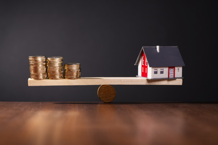 Seesaw with a house on one side and stacks of coins on the other side.