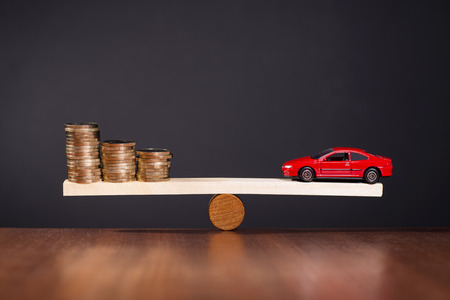 Seesaw with a car on one side and stack of money on the other side.