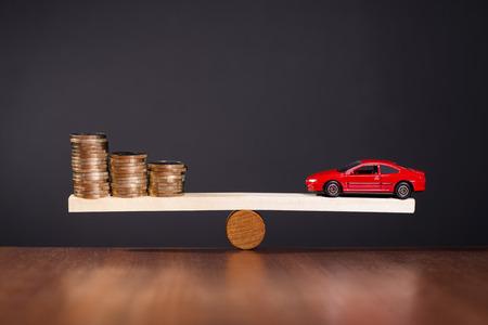 Wippe mit einem Auto auf einer Seite und Stapel von Geld auf der anderen Seite.