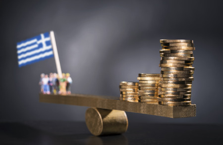 Seesaw with coins on one side and a group of people with the Greek flag on the other side. Stockfoto