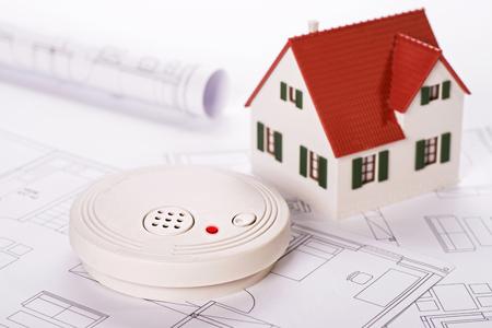 humo: Detector de humo con la casa y los planos Foto de archivo