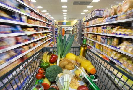 abarrotes: Cesta de la compra con los alimentos en el supermercado