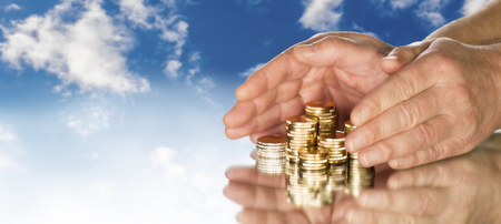 Hands include several stacks of coins in front of blue sky.