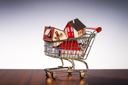 prefabricated buildings: Houses are stacked in a shopping cart Stock Photo