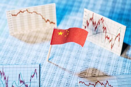 global economic crisis: Chinese flag with rate tables and graphs for economic development