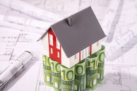 reside: House stands on 100 euro banknotes, surrounded by blueprints. Stock Photo