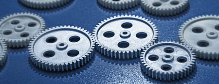 technically: Several Gear wheels in a row on blue background Stock Photo