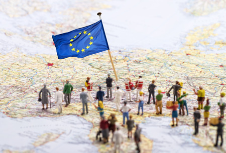 Europa mappa con bandiera europea e un grande gruppo di figure. Archivio Fotografico