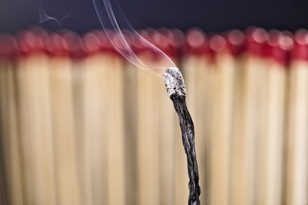 exitus: Burned matchstick in front of a new set of matches Stock Photo