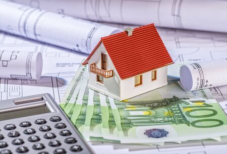 mortgaging: House with bills, plans and calculator Stock Photo