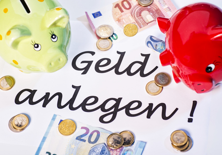 frugality: Two piggy banks with euro coins and notes and the words invest money!.