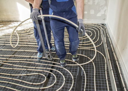 Craftsmen when laying pipes of underfloor heating Stock Photo