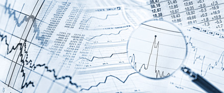 Stock quotes, price charts and a magnifying glass with stock price in detail. Archivio Fotografico