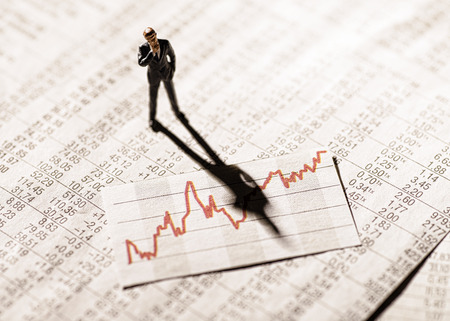 Model figure stands on rate tables and looks skeptically on a graph with stock prices. Stok Fotoğraf