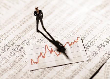 Modell Figur steht auf Tariftabellen und schaut skeptisch auf ein Diagramm mit Aktienkursen. Lizenzfreie Bilder